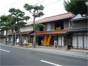 空き家の様子:神門通りから2軒の町家を見る (左奥:木塀が立てられた閉鎖的な民家、右手前:元店舗の町家)